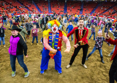 Children from the audience dancing with the clown in the arena