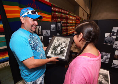 Man discussing old photo at a vendor table with Aboriginal artwork and trinkets
