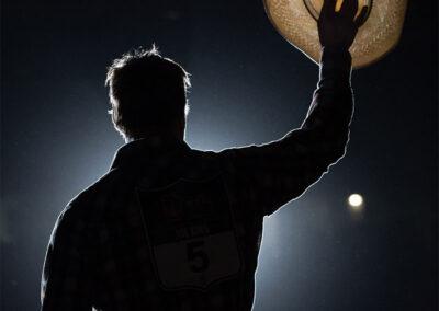 Man holding up cowboy hat