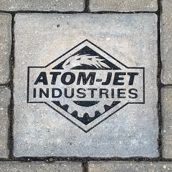 Atom-Jet Industries logo on a 11x11 stone